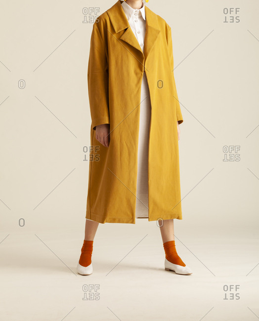 Studio shot of a model wearing a yellow coat