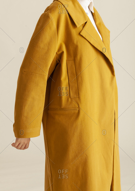Detail shot of model in a studio wearing a yellow coat