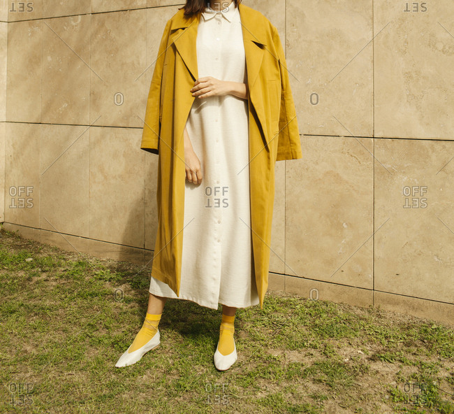 Model wearing a yellow coat outdoors