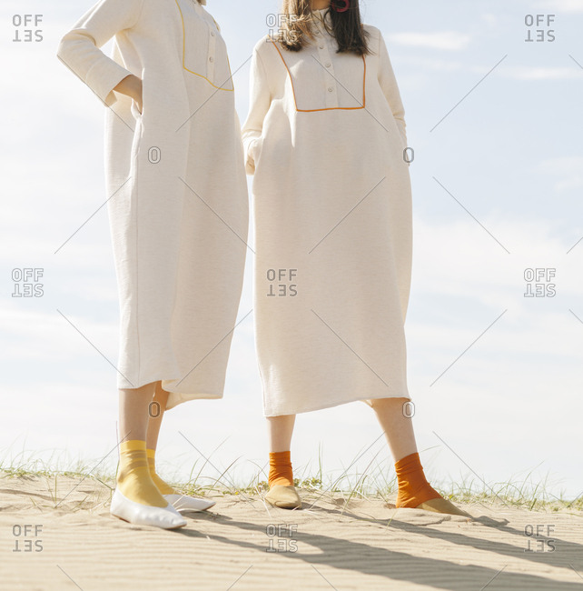 Two models wearing white dresses
