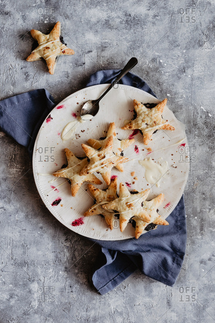 Star hand pies onto a white plate and blue napkin