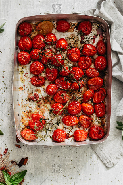 Roasted juicy cherry tomatoes into a baking tray