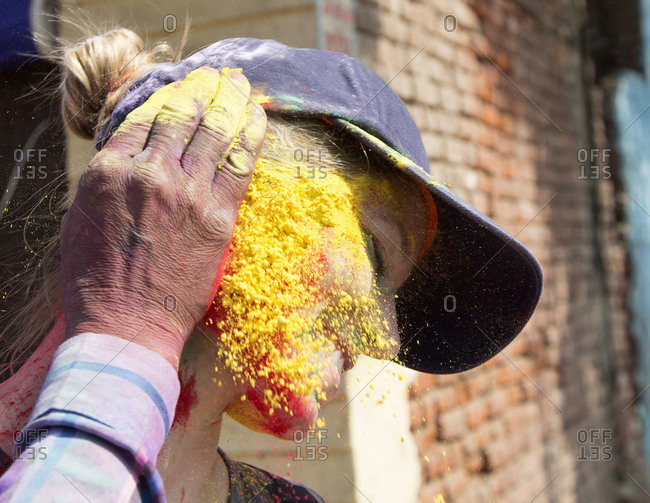 Mathura, India - March 5, 2015: Close up of a western tourist with holy powder on face during the Holi celebrations