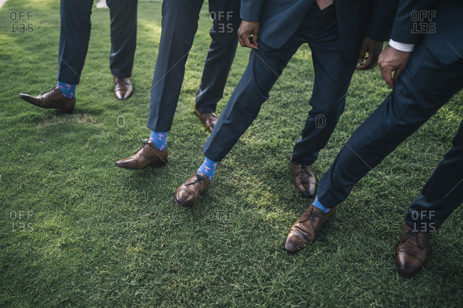 Hoi An, Vietnam - April 28, 2018: Matching suits, socks, and shoes on groomsmen