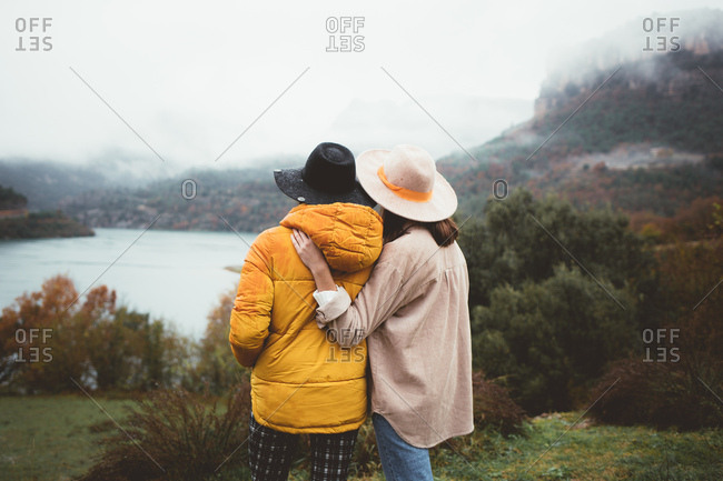 Two women with hat standing by a lake