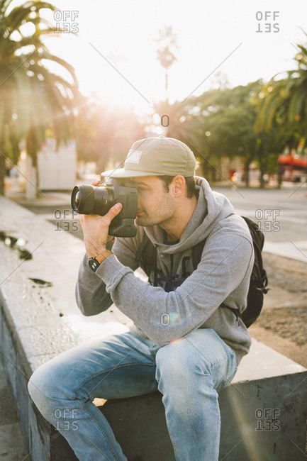 Man taking picture in the city with sunset behind