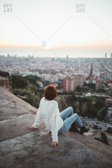 Woman sitting on a balcony looking at a cityscape, Barcelona