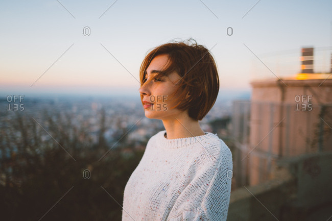 Woman looking at the sun rising in Barcelona city lookout