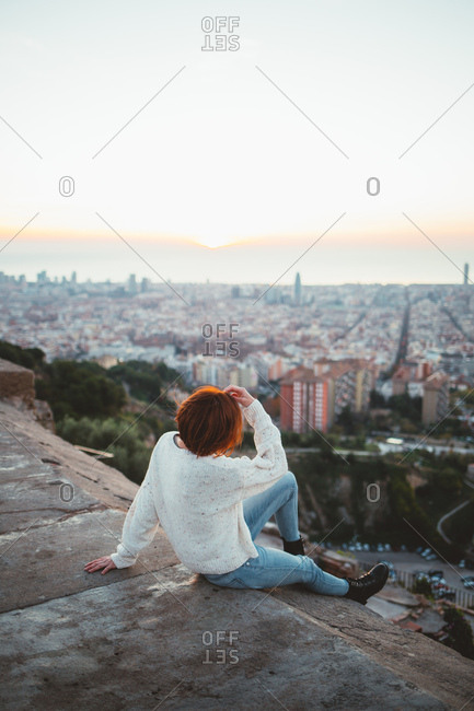 Woman sitting on a balcony looking at Barcelona, Spain cityscape from Bunkers