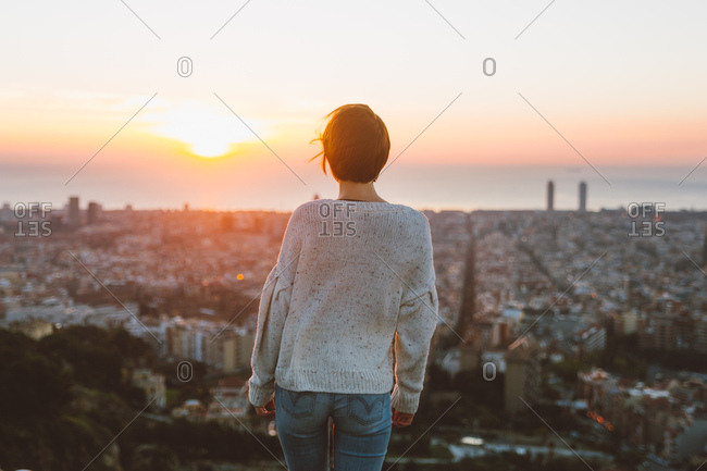 Woman looking at the sunrise in Barcelona city lookout