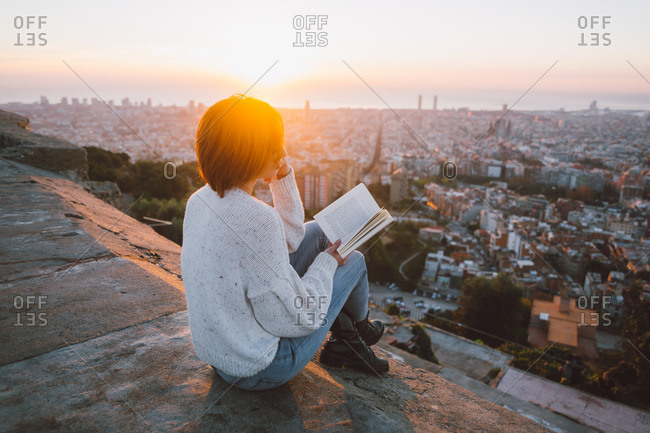 Woman reading at a city lookout