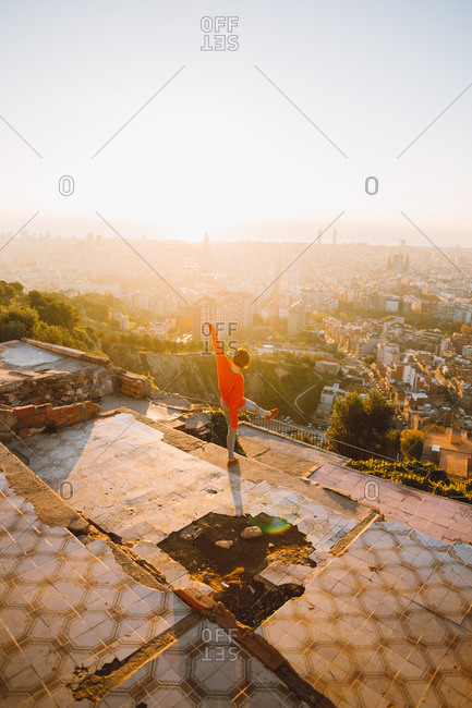 Woman standing at a lookout raising one foot