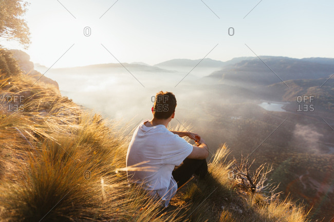 Man sitting on top of hill watching sunrise