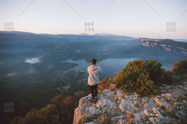 Back view of unrecognizable person standing on rock and admiring view of majestic lake