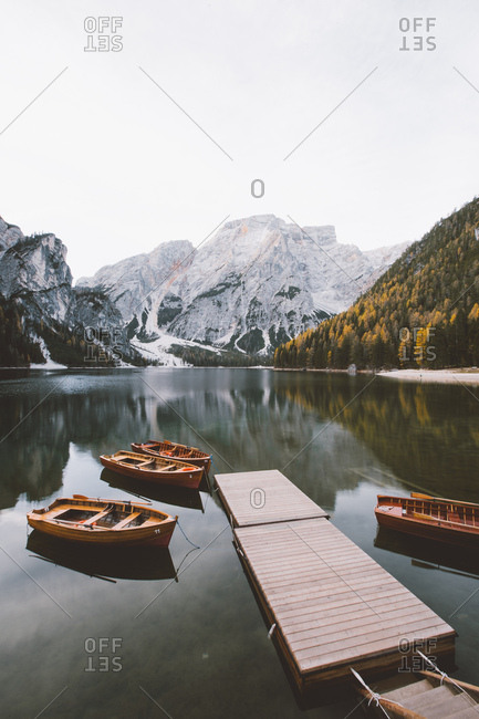 Picturesque view of small pier and boats on calm lake mountain and snow, Lago di Braies, Italy