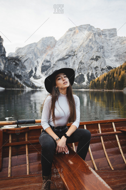 Pretty young woman, sitting on a boat on a lake surrounded by mountains