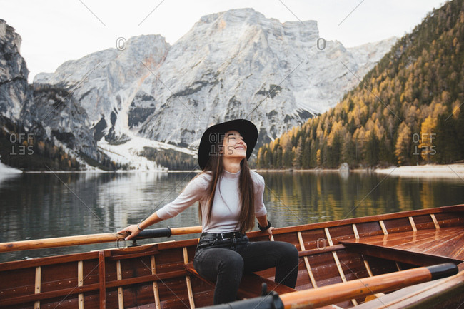 Happy young woman, sitting on a boat on a lake surrounded by mountains