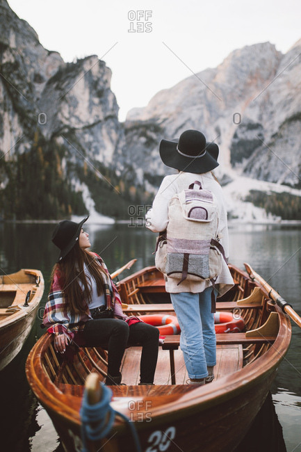 Two women on a wooden boat looking at a majestic landscape