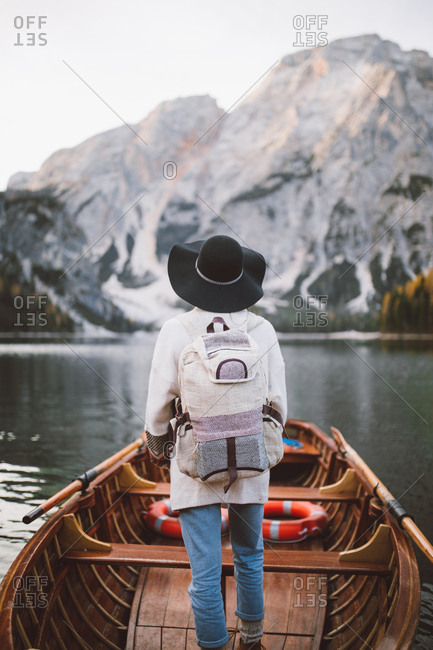 Woman on a wooden boat looking at a majestic landscape