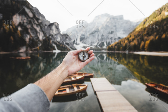 Hand of person standing in lake and holding compass