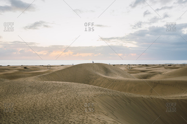 Man standing on top of a dune looking the sun rise