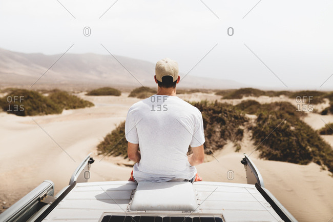 Man sitting on top of a van with desert in front