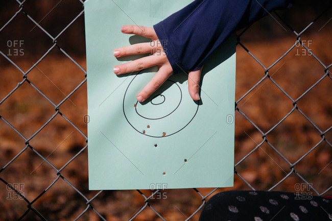 A girl points to a hole in a target