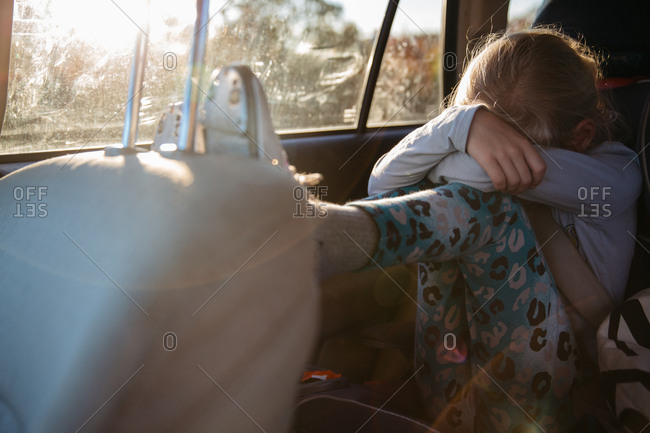 Girl pouting in car with tap shoes on and sunlight pouring in