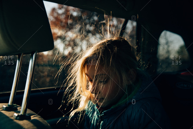 A girl in car with static hair lit up by the sun