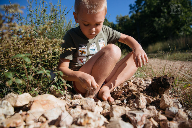 Boy plays in rocks on edge of dirt country road in summer