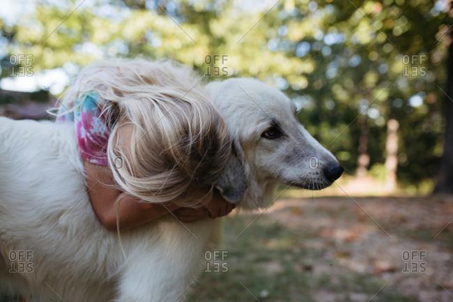 Blond girl hugs her white dog outside