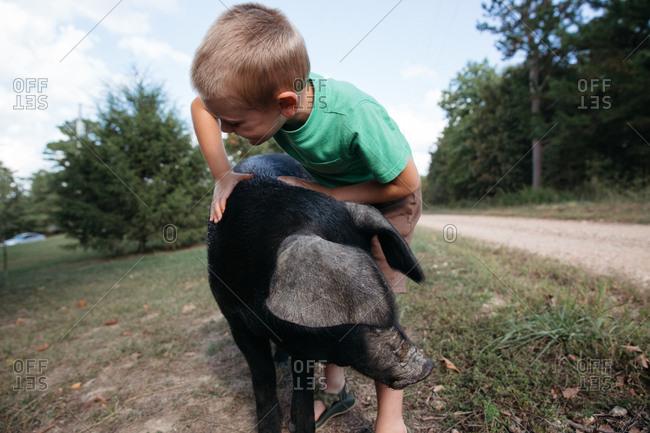 A boy hugs a big black pig near a dirt road