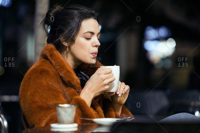 Night scene of elegant woman having a tea on a terrace