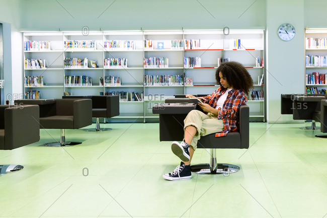 Young woman reading a book in the library.