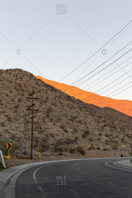 Power lines in Palm Springs next to a road with a setting sun reflected on the mountains behind it.