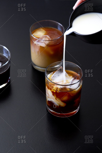 Milk pouring into glass of cold brew