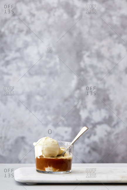 Vanilla ice cream in a glass with coffee and spoon