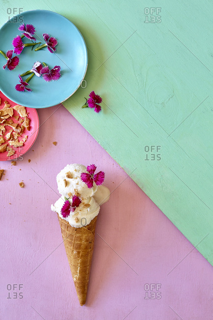 Vanilla Ice-Cream scoops in sugar cone with toppings on colorful background