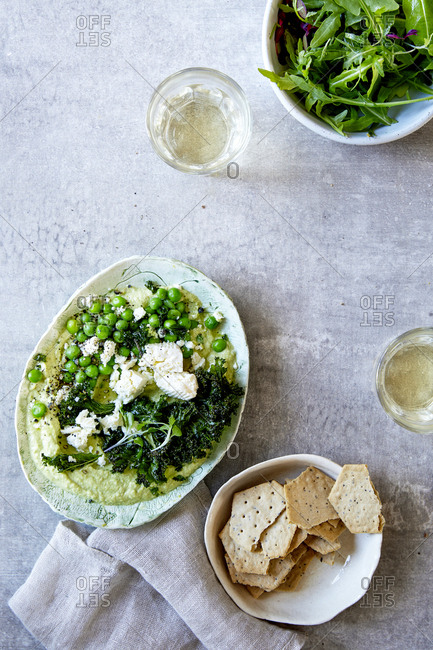 Pea hummus with rocket salad, wine and crackers