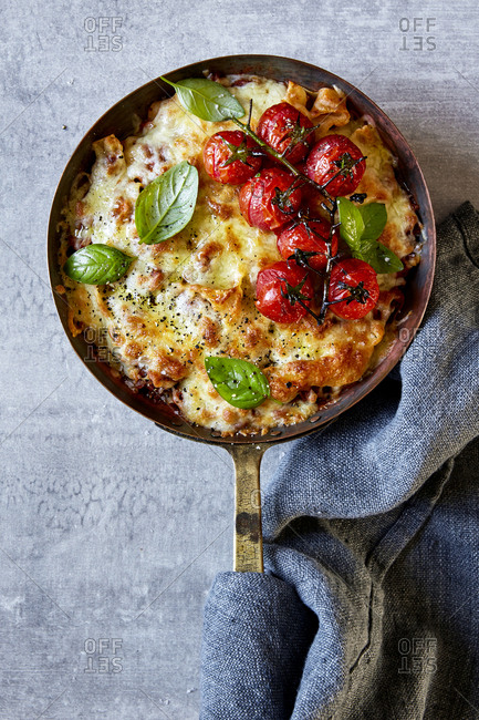 Skillet lasagna with vine tomatoes, basil and kitchen cloth