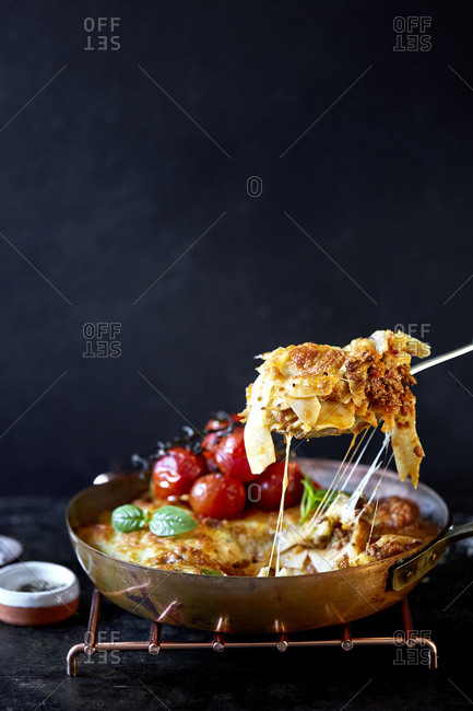 Spoon of cheesy baked pappardelle ragu