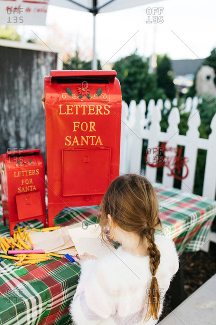 Young girl writing a letter to santa at a christmas marker