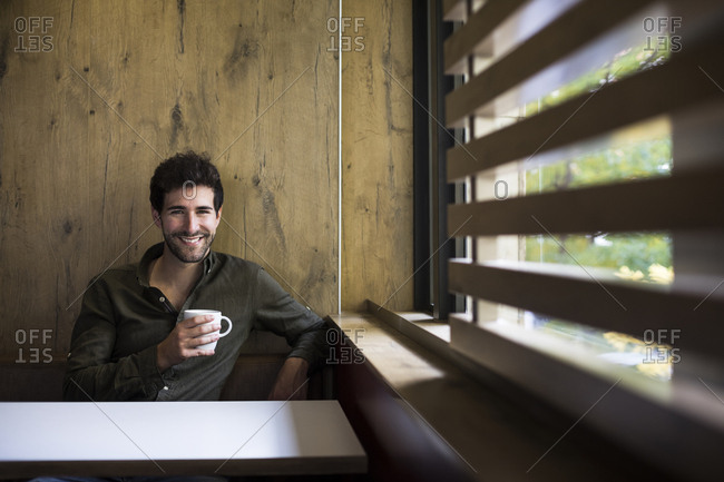 Portrait of a man smiling drinking a coffee and looking at camera in a cafe in Madrid, Spain.