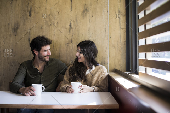 Man and woman talking and drinking coffee in a cafe in Madrid, Spain.