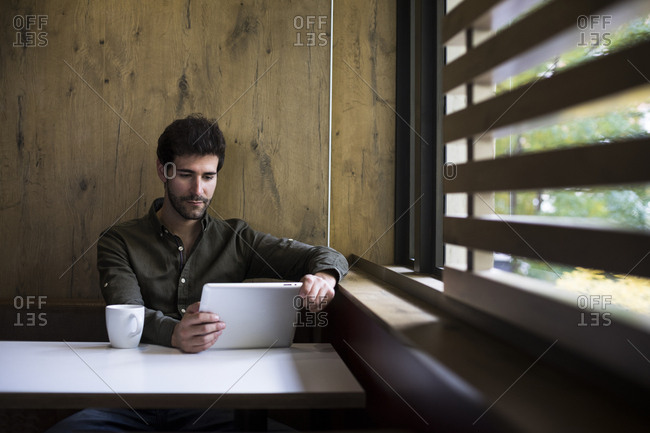 Man using a tablet in a cafe in Madrid, Spain.