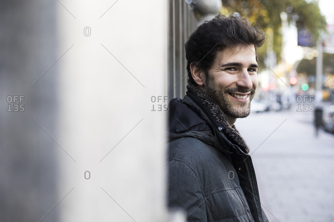 Man smiling looking at camera in a street in Madrid, Spain.