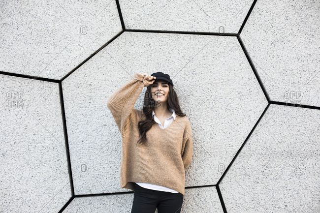Beautiful woman smiling touching her hat leaning against a wall in Madrid, Spain.