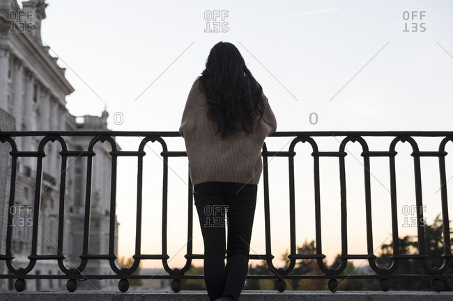 Woman leaning on a fence at sunset in Madrid, Spain.