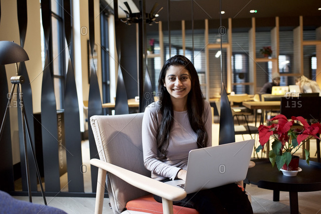 Smiling young Asian woman with a laptop computer sitting in a contemporary office
