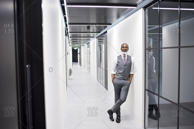 Businessman leaning against the wall in a modern office
